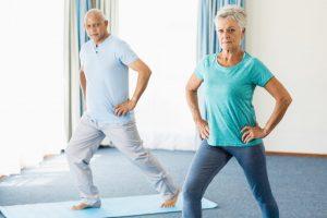Seniors doing sport exercises in a studio